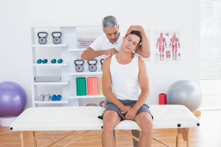 muscle retraining: Doctor examining his patient neck in medical office
