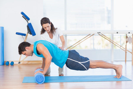 Trainer working with man on exercise mat in fitness studio Foto de archivo