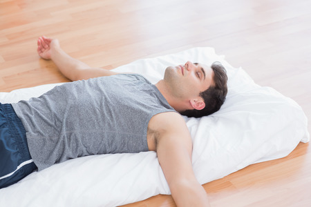 young adult men: Man relaxing on exercise mat in fitness studio