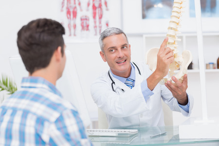 anatomical: Doctor explaining anatomical spine to his patient in medical office