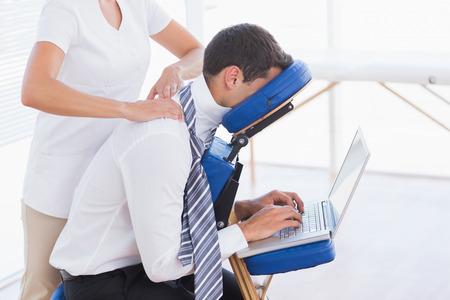 masaje: El hombre de negocios con masaje de espalda durante el uso de la computadora port�til en la oficina m�dica