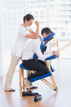 massage homme: Homme d'affaires ayant massage du dos dans le cabinet médical Banque d'images