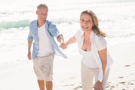 Feliz pareja sonriendo a la cámara en la playa Foto de archivo - 44845136