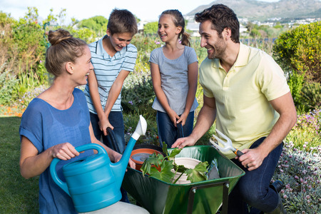 family gardening: Happy young family gardening together in the garden