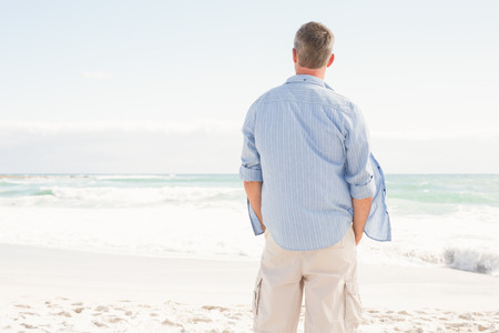 escapism: Man looking out to sea at the beach
