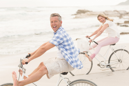 Casual couple on a bike ride at the beach Stock Photo