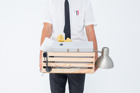 belongings: Fired businessman holding box of belongings on white background