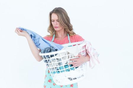 lavando ropa: Mujer que mira la ropa sucia en el fondo blanco