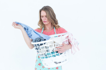 washing clothes: Woman looking at dirty clothes on white background Stock Photo