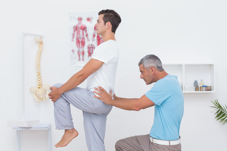 Doctor examining his patient back in medical office photo