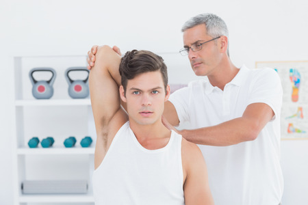 medical office: Doctor stretching a young man arm in medical office