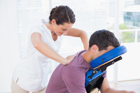 chair massage: Man having back massage in medical office