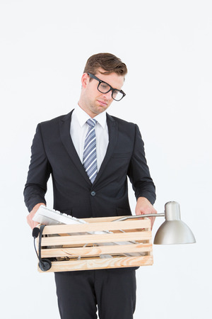 redundant: Sad geeky businessman holding box of his things on white background