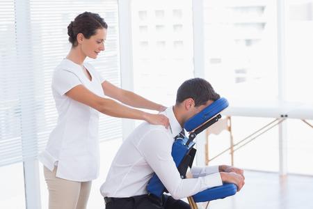 Businessman having back massage in medical office