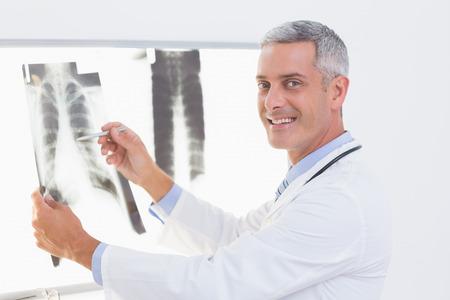 carita feliz: Doctor sonriente mirando a Rayos-X en el consultorio m�dico Foto de archivo