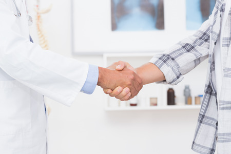Patient shaking hands with doctor in medical office photo
