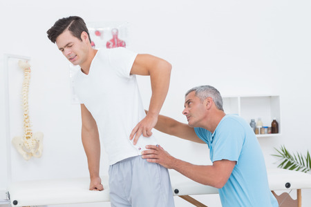 hand on hip: Doctor examining his patient back in medical office Stock Photo