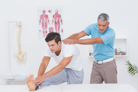 retraining: Doctor examining his patient back in medical office Stock Photo