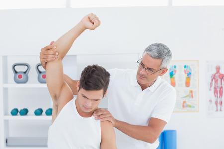 fisioterapia: M�dico estirar un brazo de hombre joven en el consultorio m�dico