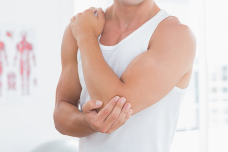 Young man suffering from elbow pain in medical office