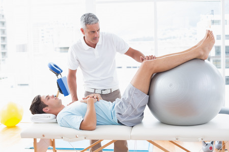 personal injury: Therapist helping his patient with exercise ball in medical office Stock Photo