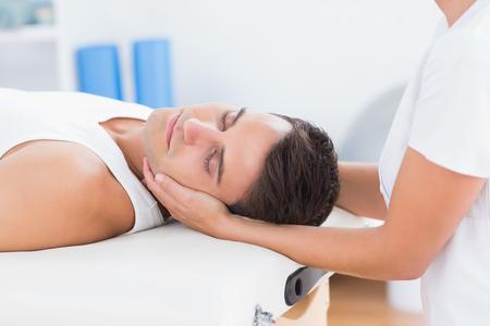 cabeza de mujer: El hombre que recibe masaje de cuello en el consultorio médico