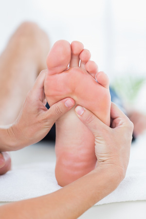 Man having foot massage in medical office photo