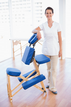 Smiling therapist standing with massage chair in medical office Stock Photo