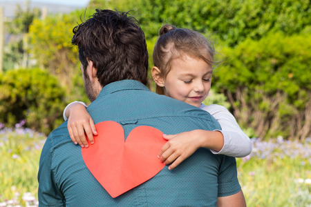 Daughter giving dad a heart card in the countryside