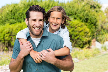 Father and son smiling at camera in the countryside