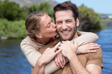 man woman kissing: Happy couple at a lake in the countryside Stock Photo