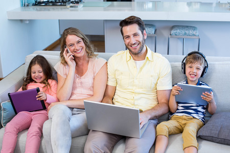 Happy family on the couch together using devices at home in the living room Stock Photo