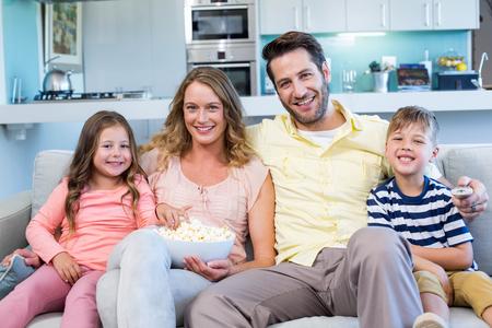 convivencia familiar: Familia feliz en el sof� viendo la televisi�n en su casa en la sala de estar Foto de archivo