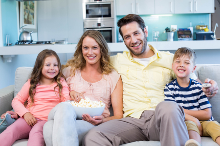 family with two children: Happy family on the couch watching tv at home in the living room Stock Photo