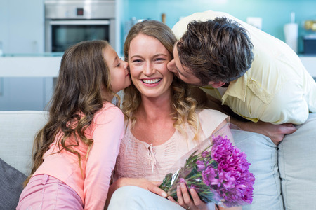 girls kissing girls: Daughter surprising mother with flowers at home in the living room