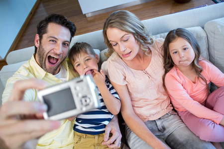 Happy Family Taking Selfie On Couch At Home In The Living Room Stock ...