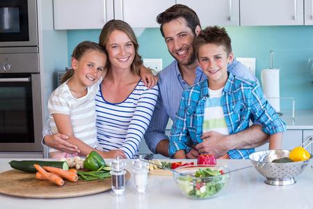 convivencia familiar: Familia feliz que se prepara verduras juntos en casa en la cocina