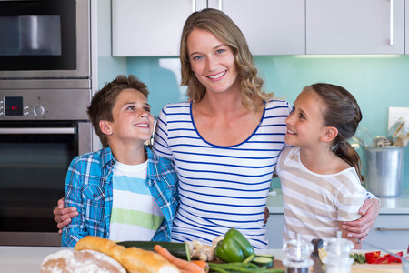 Happy family preparing vegetables together at home in the kitchen photo