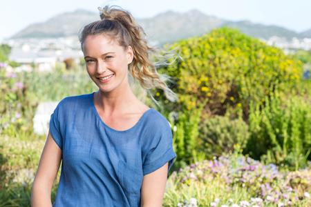 femmes souriantes: Jolie blonde souriante à la caméra dans le jardin Banque d'images