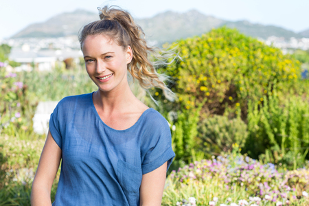 Pretty blonde lachend in de camera in de tuin