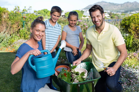 Happy young family gardening together in the garden photo