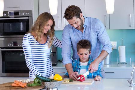 cuchillo de cocina: Familia feliz que se prepara verduras juntos en casa en la cocina