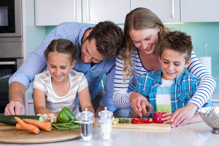 life at home: Happy family preparing vegetables together at home in the kitchen