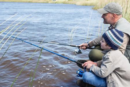 pesca: Padre e hijo de pesca en un lago en el campo Foto de archivo