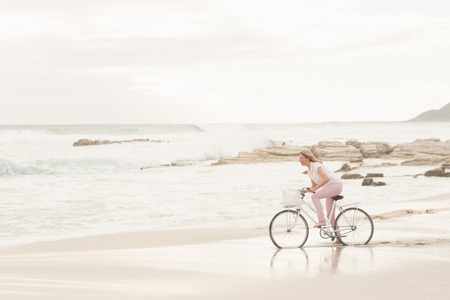 escapism: Casual woman on a bike ride at the beach Stock Photo