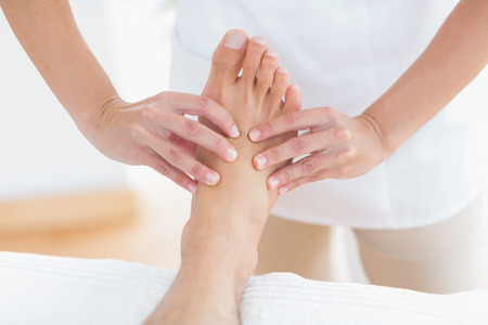 massage table: Physiotherapist doing foot massage in medical office Stock Photo