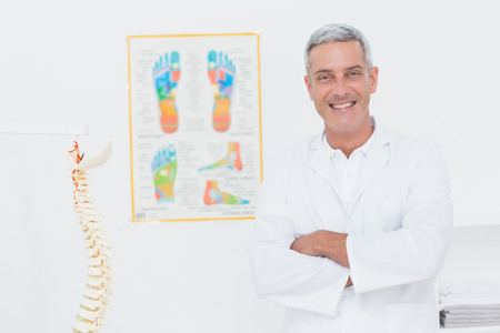 Happy doctor smiling at camera with arms crossed in medical office photo
