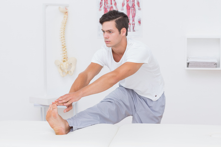 postural integration: Patient stretching his leg on bed in medical office Stock Photo