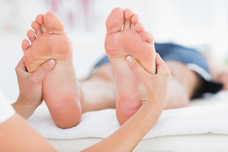 adult foot: Man having feet massage in medical office Stock Photo
