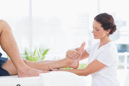 fisioterapia: Fisioterapeuta haciendo masaje de piernas en el consultorio médico Foto de archivo